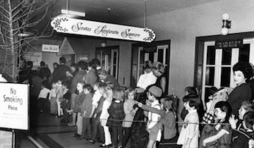 Parents wait with children in a long line to see Santa on the 12th floor Christmas fantasy land in the downtown J.L. Hudson's store, Dec. 12, 1968. The excited children and their parents received photo keepsakes of their tots on Santa's lap. Little did they know that there were several santas working together to keep the lines moving.  The Detroit News.