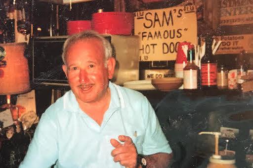 Sam behind bar gesturing