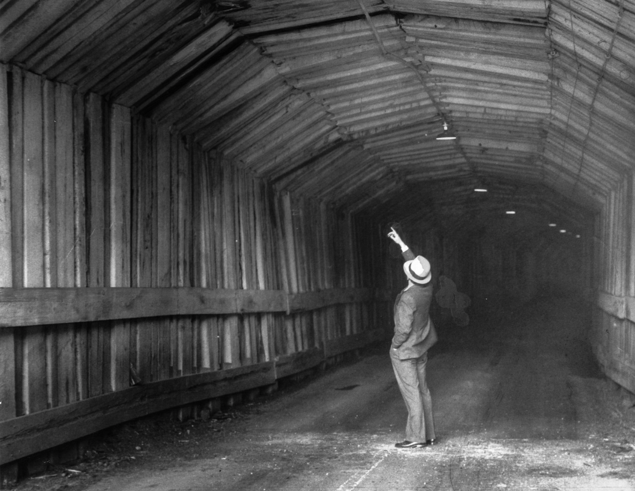 March 10, 1934 - A man points to dark spots in the ceiling of the old tunnel where timbers fell earlier in the day. They had weakened by years of water damage. (Oakland Tribune Photo)